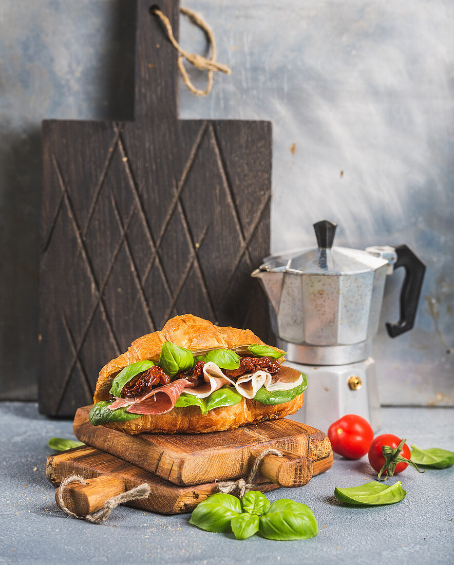 Croissant sandwich with smoked meat Prosciutto di Parma, sun dried tomatoes, fresh spinach and basil