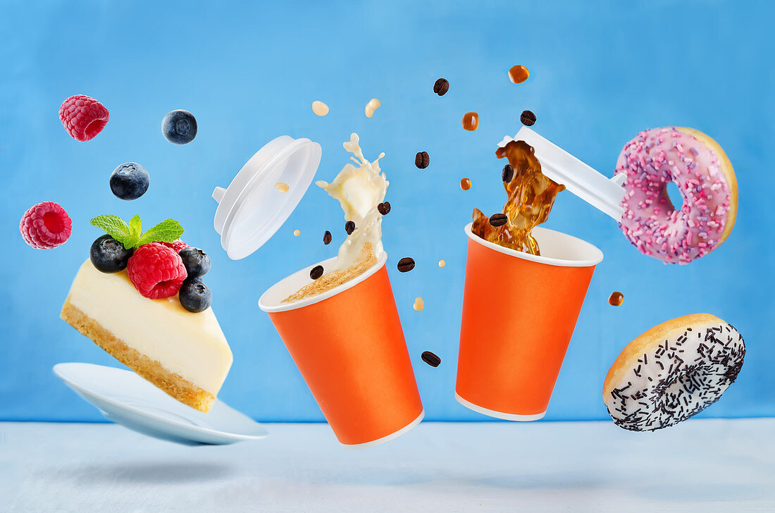 Flying glasses of coffee with multicolored donuts and cheesecake on a blue background