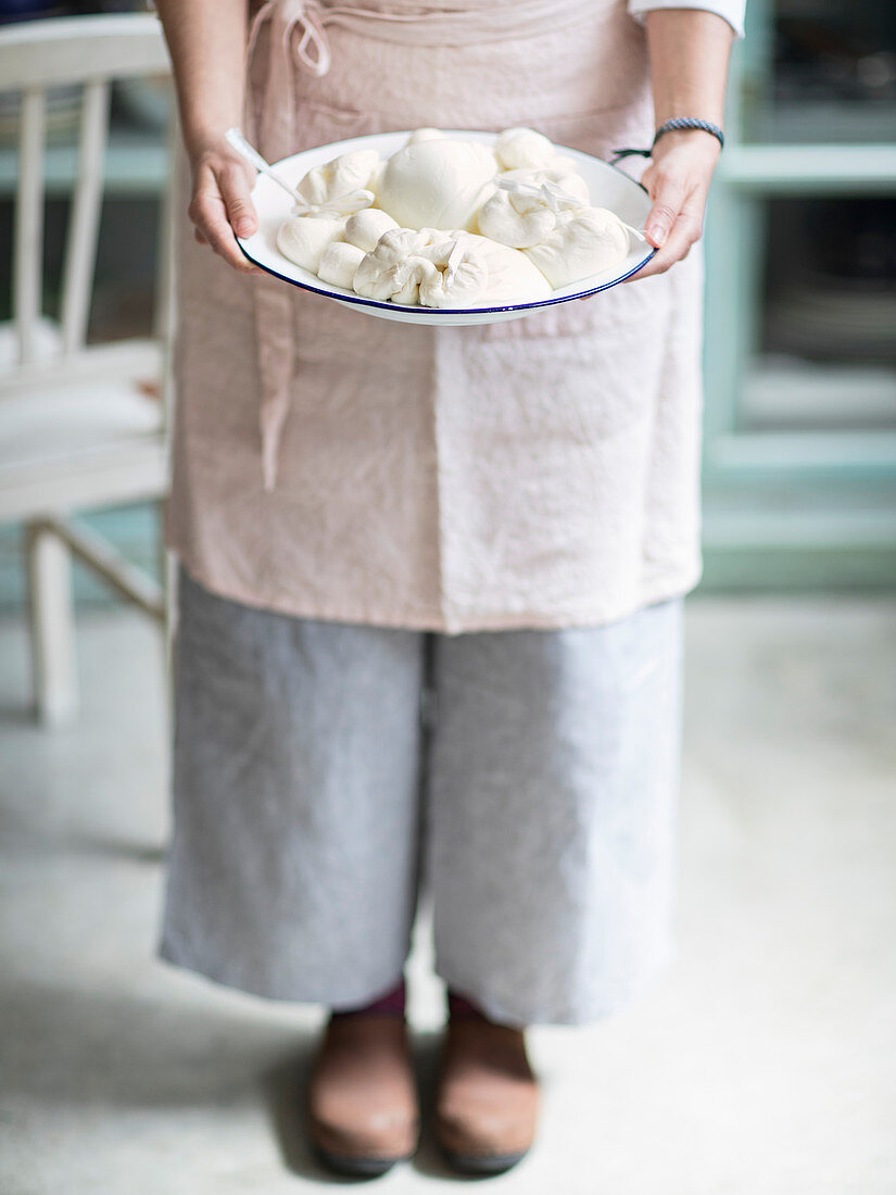 A woman holding an enamel bowl with fresh mozzarella
