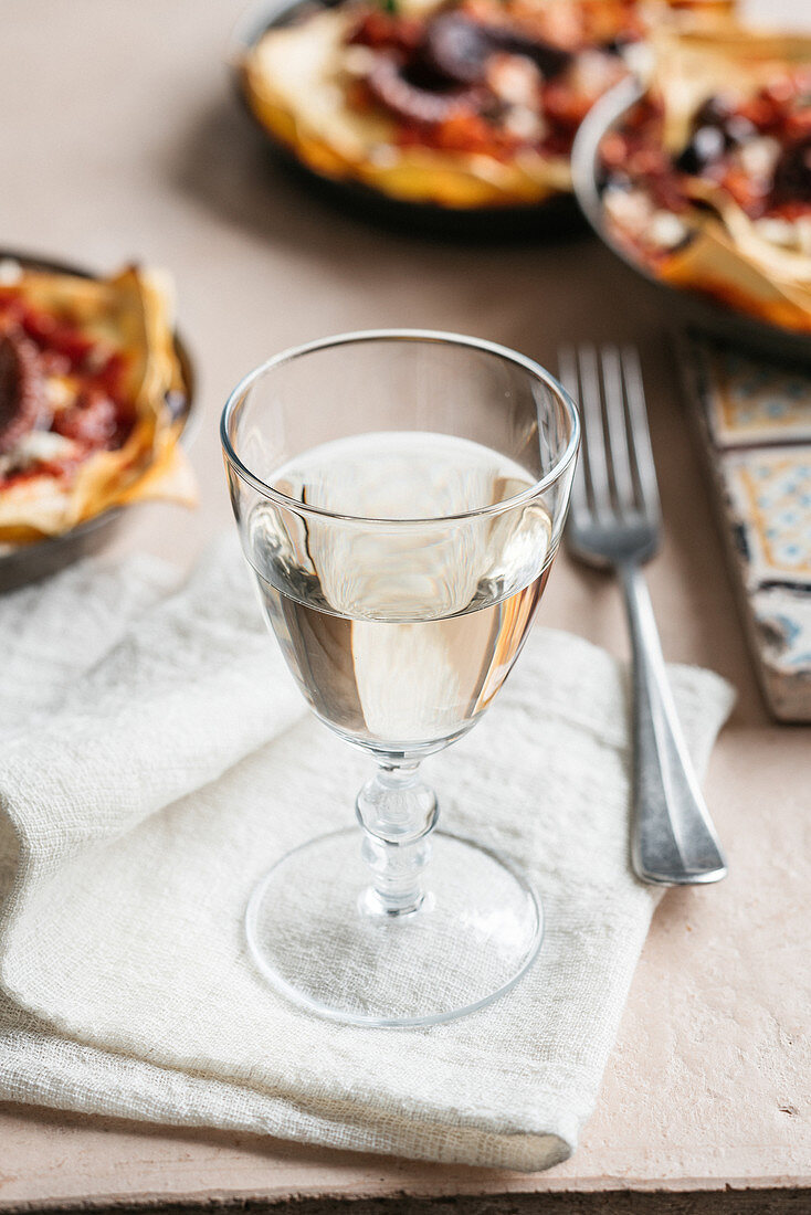 A glass of white wine on a white napkin
