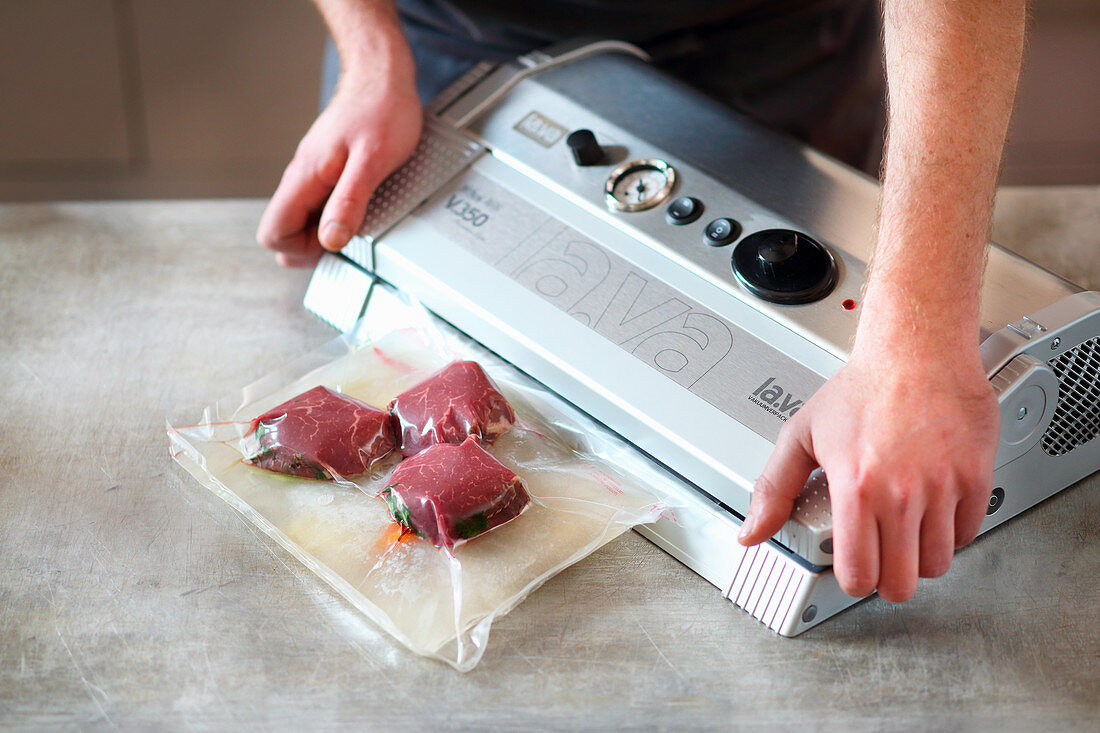 Frozen meat and juices being vacuum packed