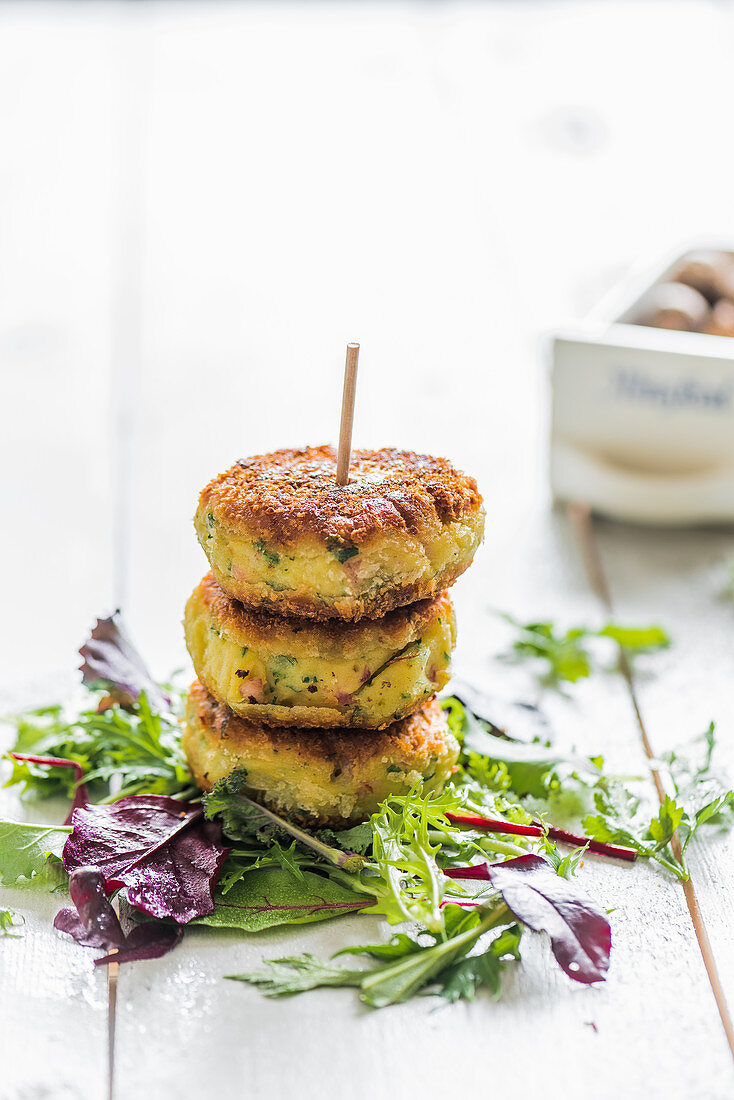 Potato fritter on a wooden stick on lettuce leaves