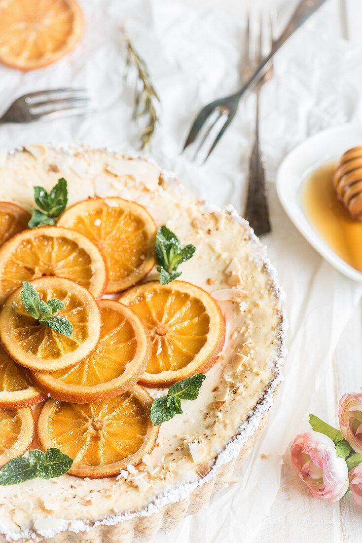 Orange tart with orange slices, yoghurt cream, mint and icing sugar