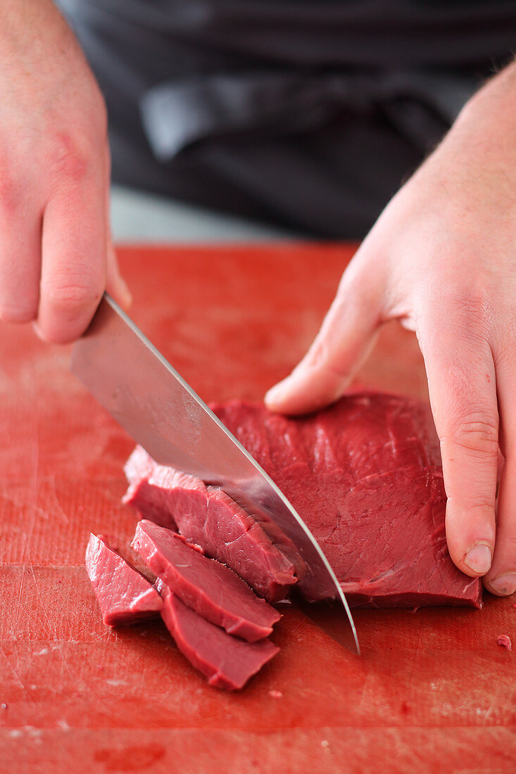 Trimmed and soaked beef heart being sliced