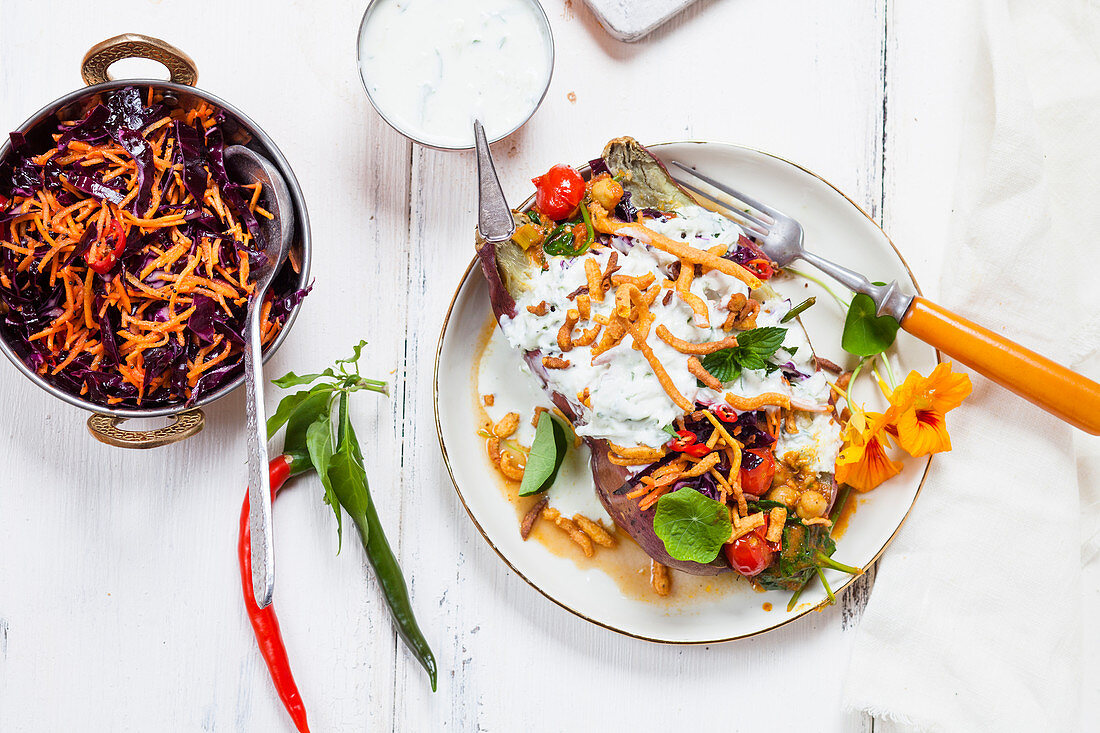 Kumpir (stuffed baked sweet potato) with spinach, carrot and red cabbage salad, raita and homemade chickpea noodles (India)