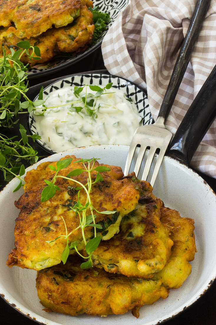 Courgette fritters with a dip and herbs in an iron pan