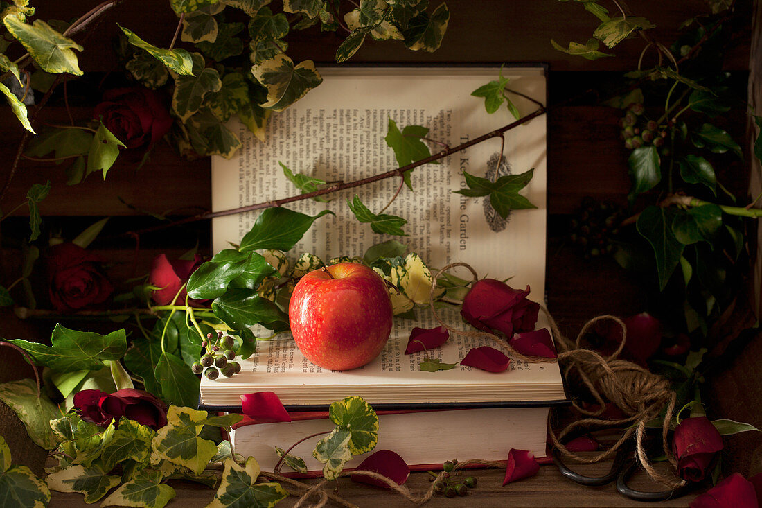 A Pink Lady Apple on Books with Roses and Ivy