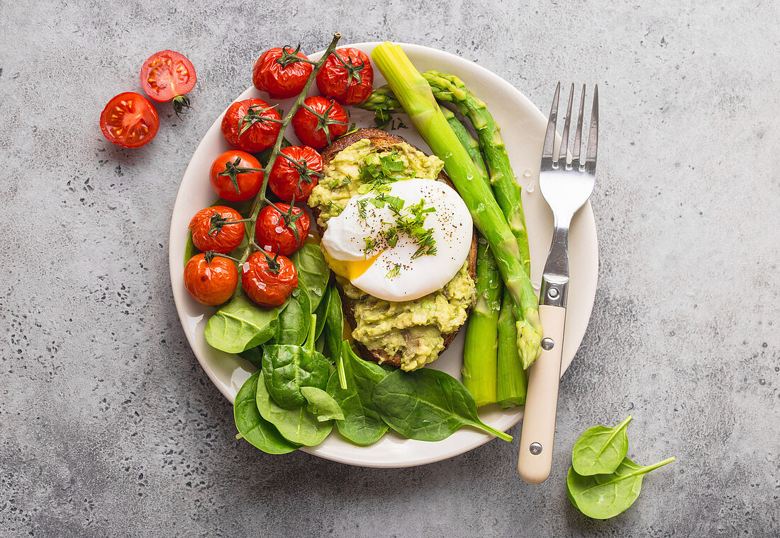 Toast with avocado cream and a poached egg served with tomatoes, spinach and asparagus