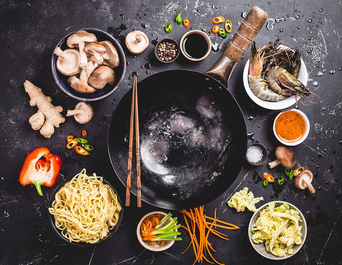 An arrangement of a wok and ingredients for an oriental noodle dish (seen from above)