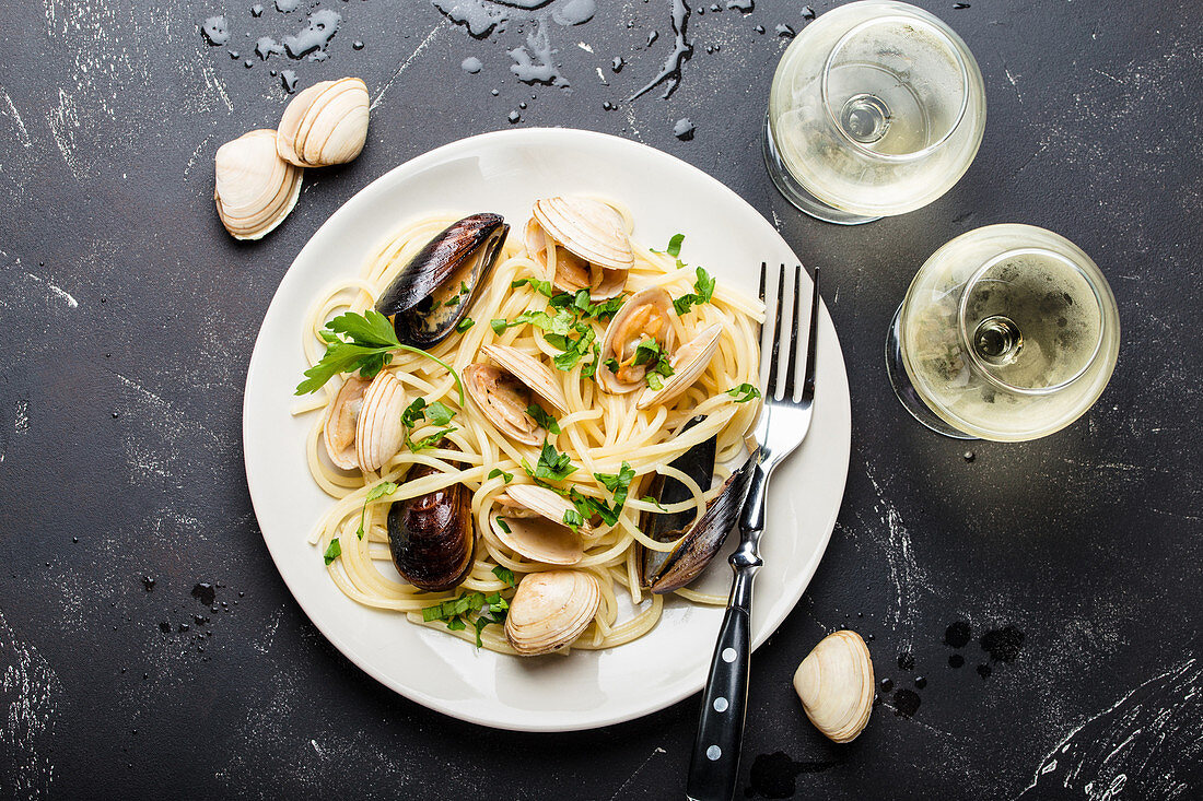 Spaghetti vongole (pasta with mussels, Italy) served with white wine
