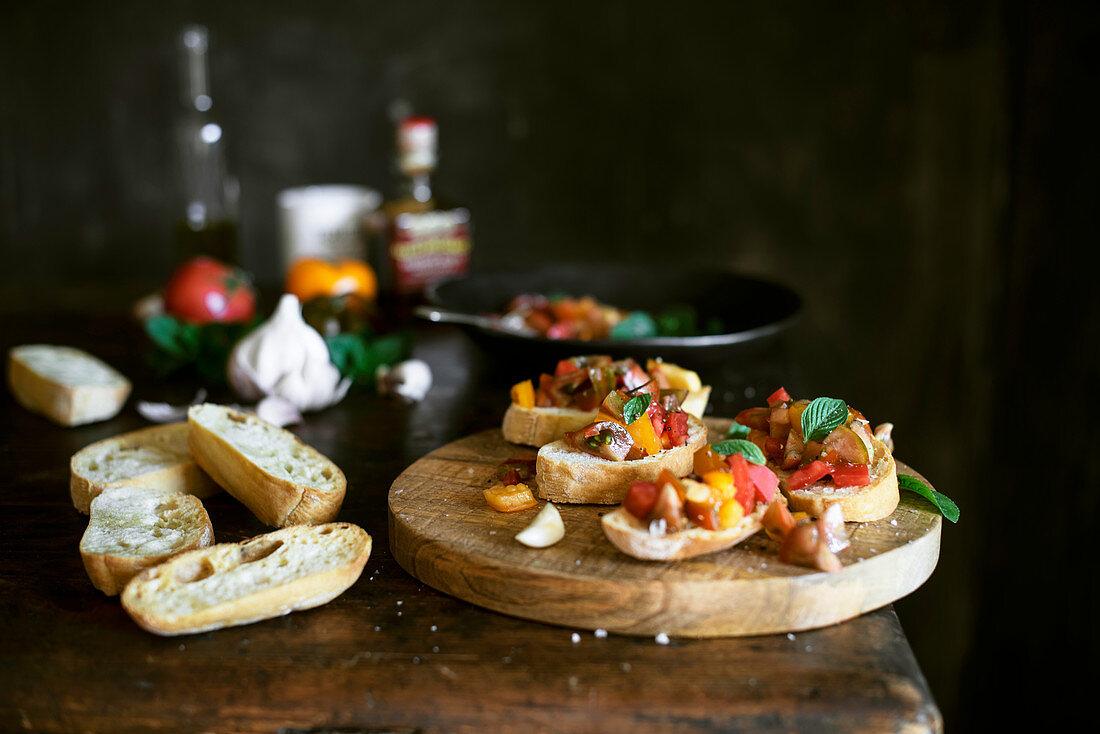 Tomato bruschetta on a wooden surface next to ingredients