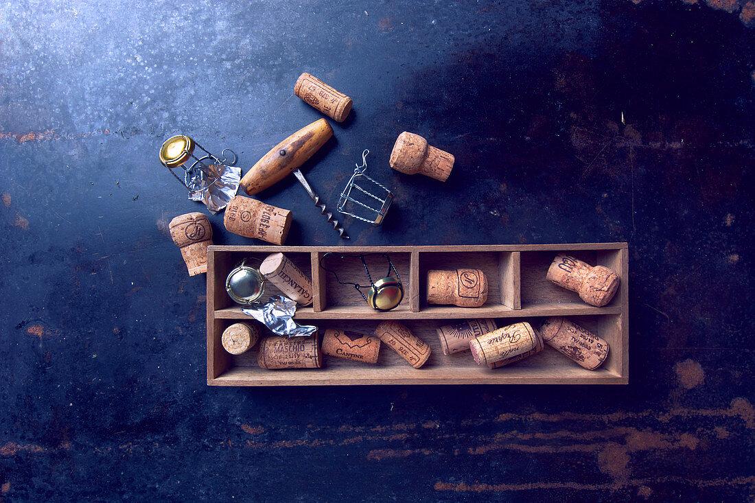 Verschiedene Flaschenkorken in Holzkästchen und Korkenzieher