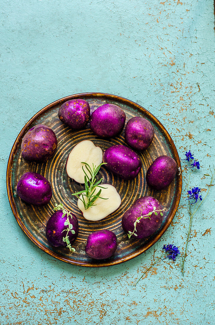 Purple potatoes with thyme and rosemary on a blue old table