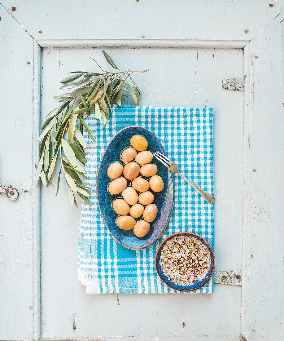 Green big olives in blue ceramic plate with spices