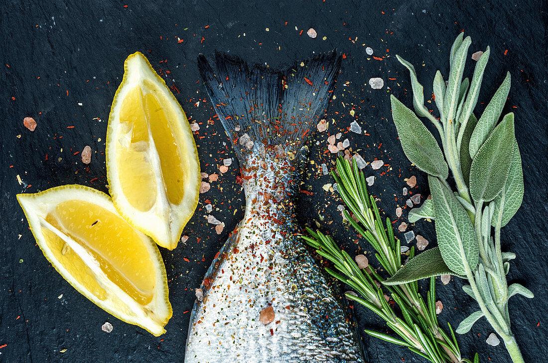 Tail of fresh raw Dorado or sea bream fish on black slate stone