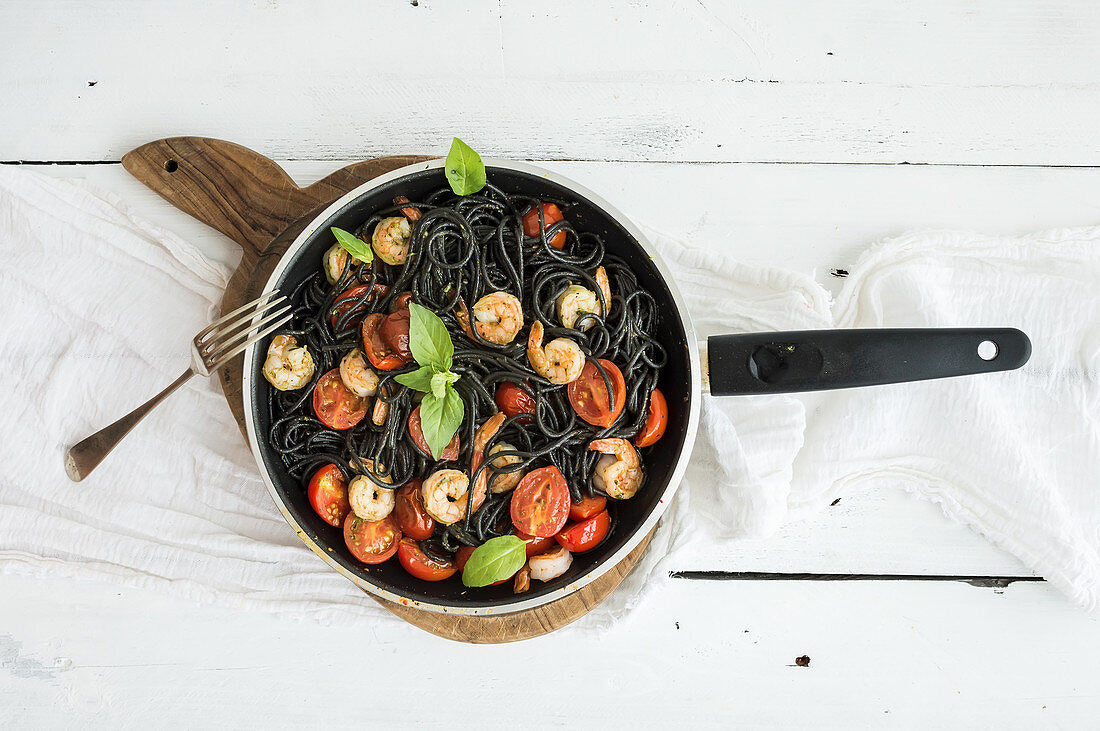 Black pasta spaghetti with shrimps, basil, pesto sauce and slow-roasted cherry-tomatoes in cooking pan on rustic chopping board over white wooden table