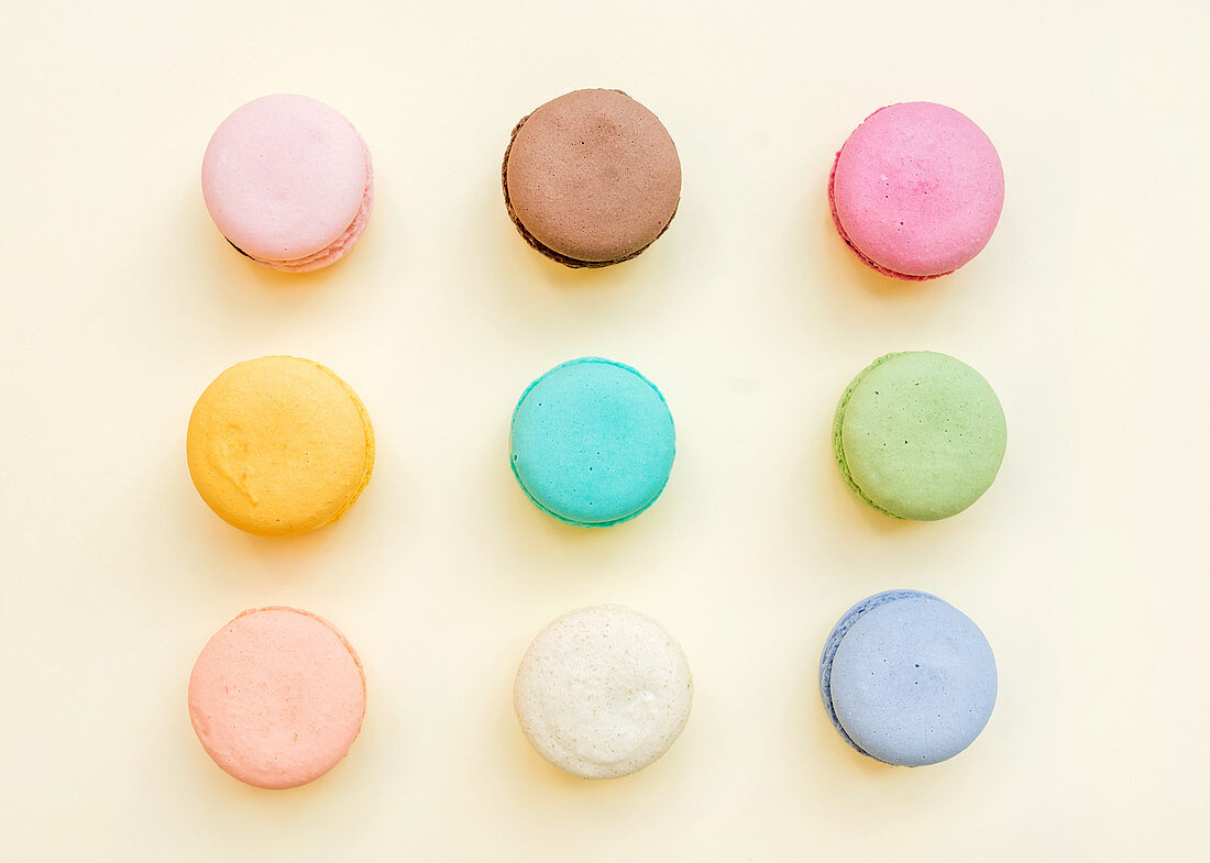 Sweet colorful French macaroon biscuits on pastel yellow background, top view