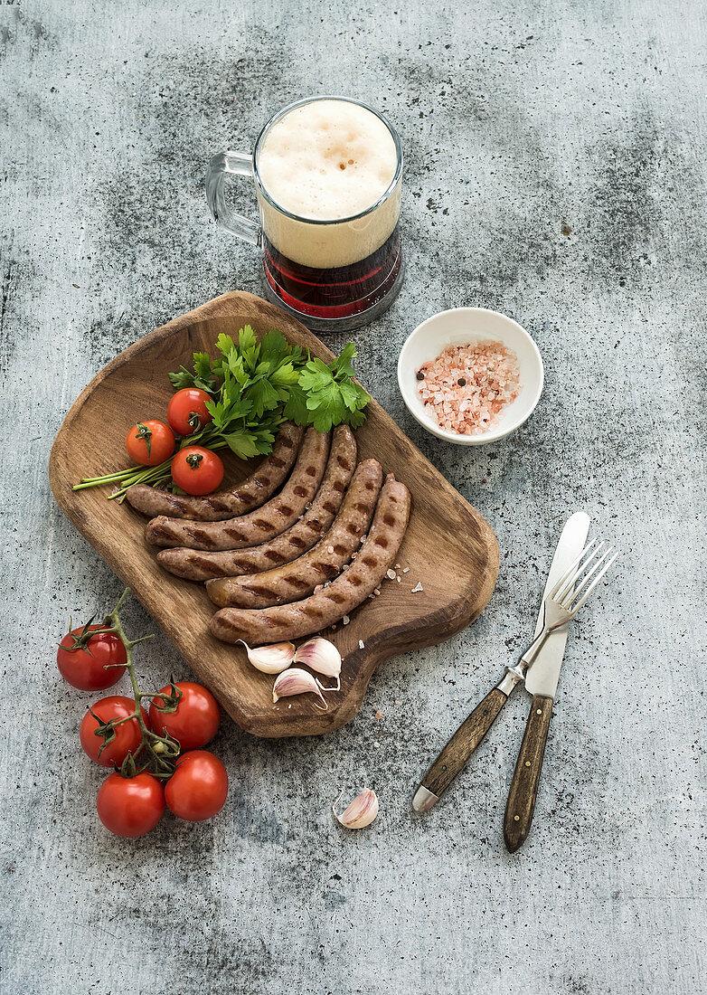 Grilled sausages with vegetables on rustic serving board and mug of light beer over grunge backdrop
