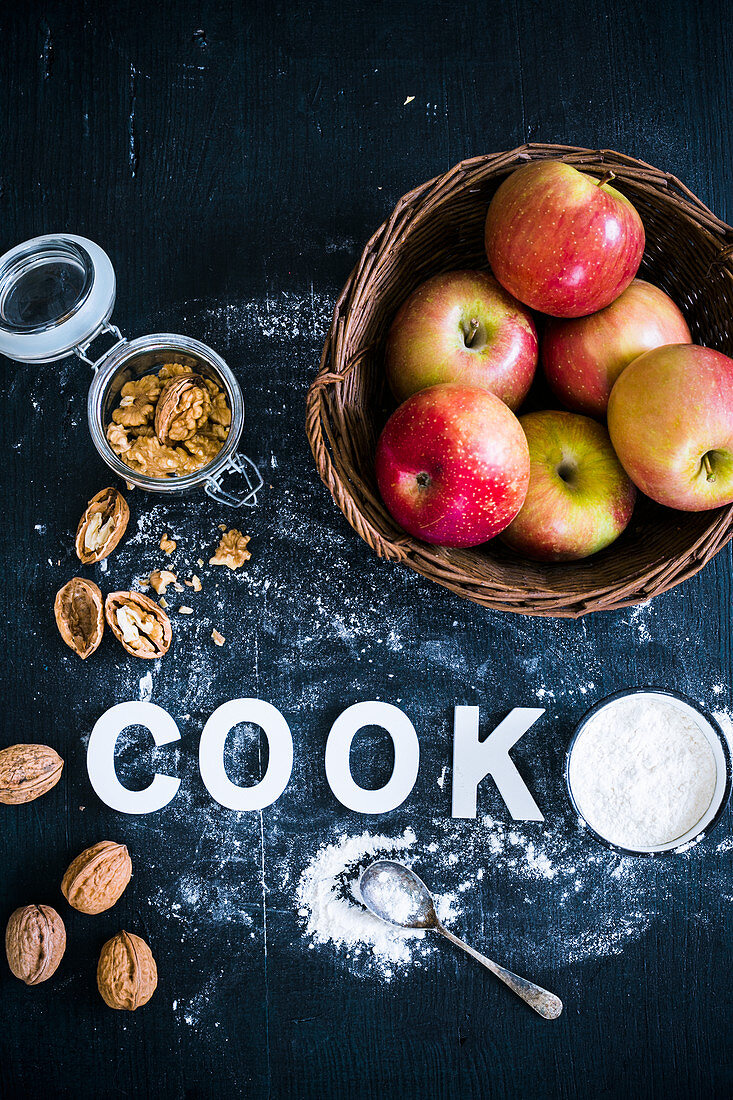 Apples in a basket with walnuts and flour