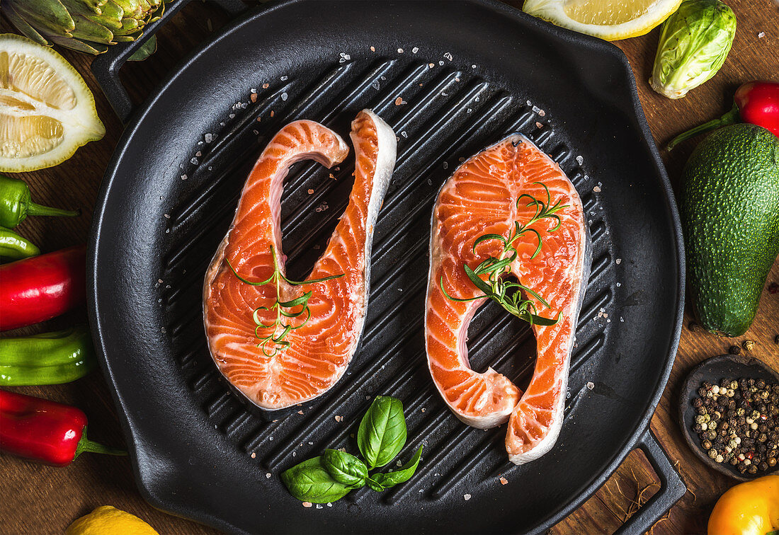 Uncooked salmon with vegetables, herbs, lemon, avocado, artichokes, spices in iron grilling pan