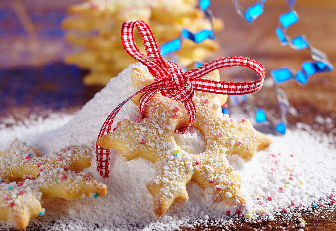 A shortbread snowflake biscuit with sugar sprinkles and icing sugar