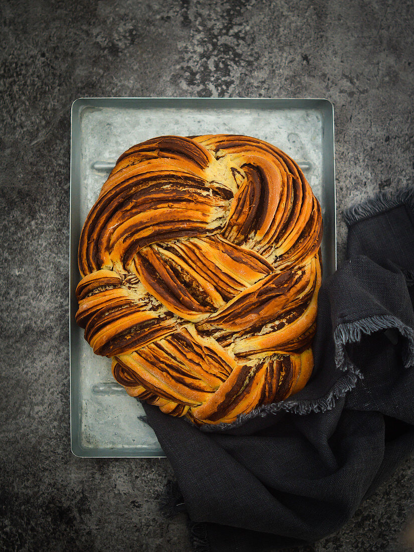 Plaited bread with chocolate and cinnamon on a baking tray