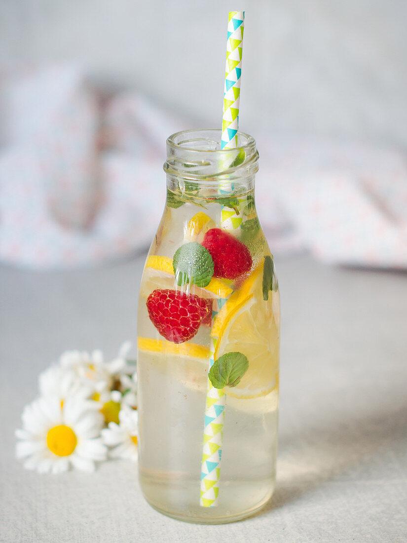 Elderflower lemonade served with fruit in a glass bottle