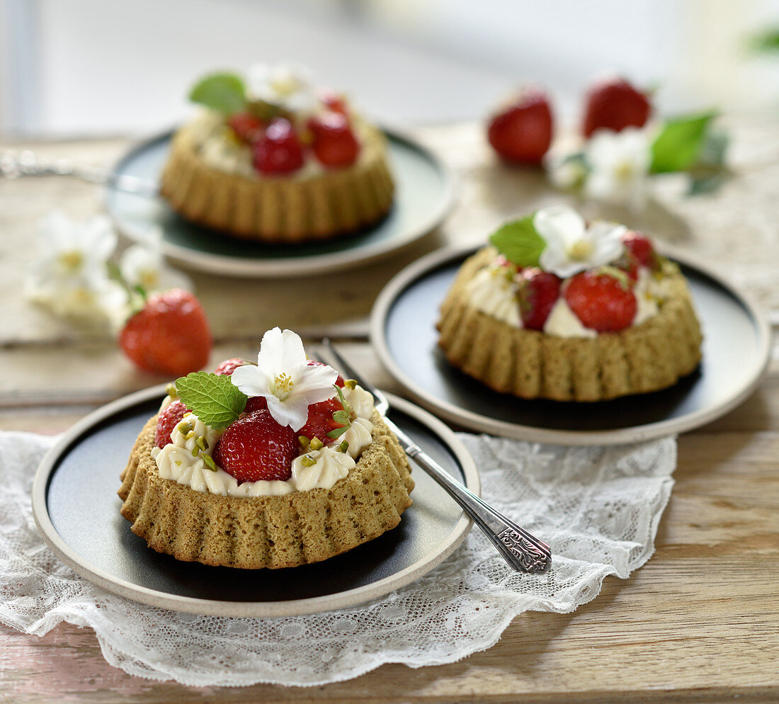 Vegan pumpkin seed and sponge cakes with white chocolate cream and fresh strawberries