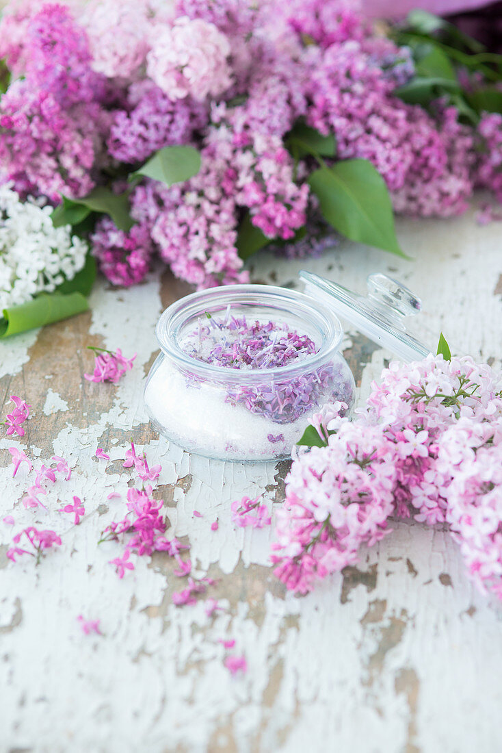 Lilac sugar and purple lilac on a white wooden surface