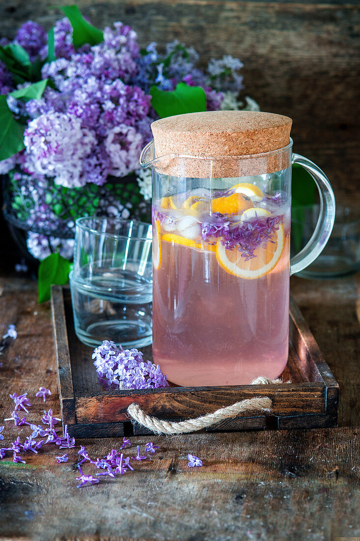 Refreshing lilac lemonade with lilac syrup, lemons and ice cubes