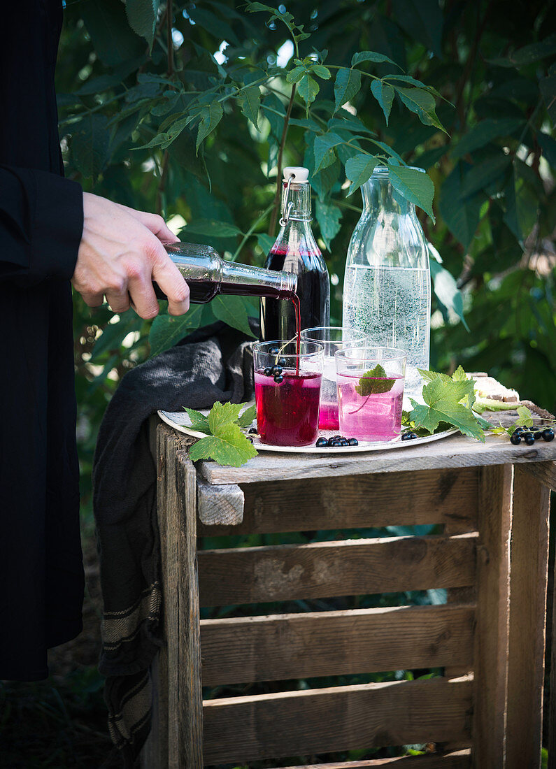 A woman preparing a refreshing drink with blackcurrant syrup