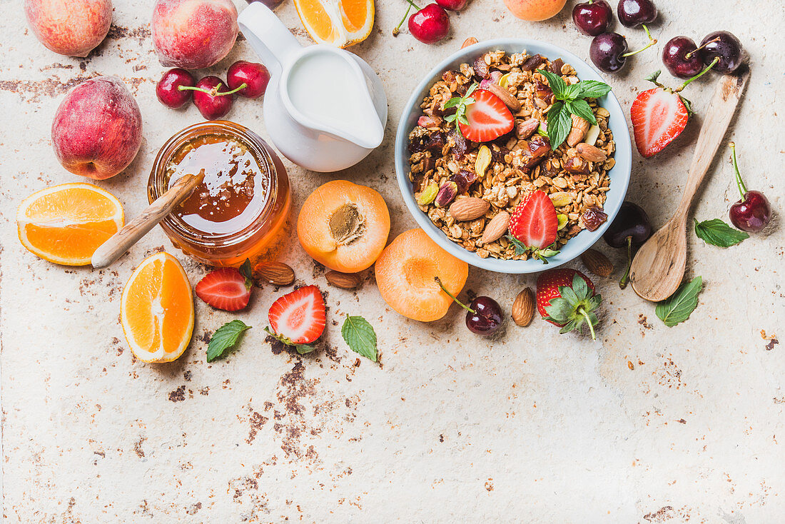 Healthy breakfast ingredients - Oat granola in bowl with nuts, strawberry and mint leaves, fresh fruits, berries