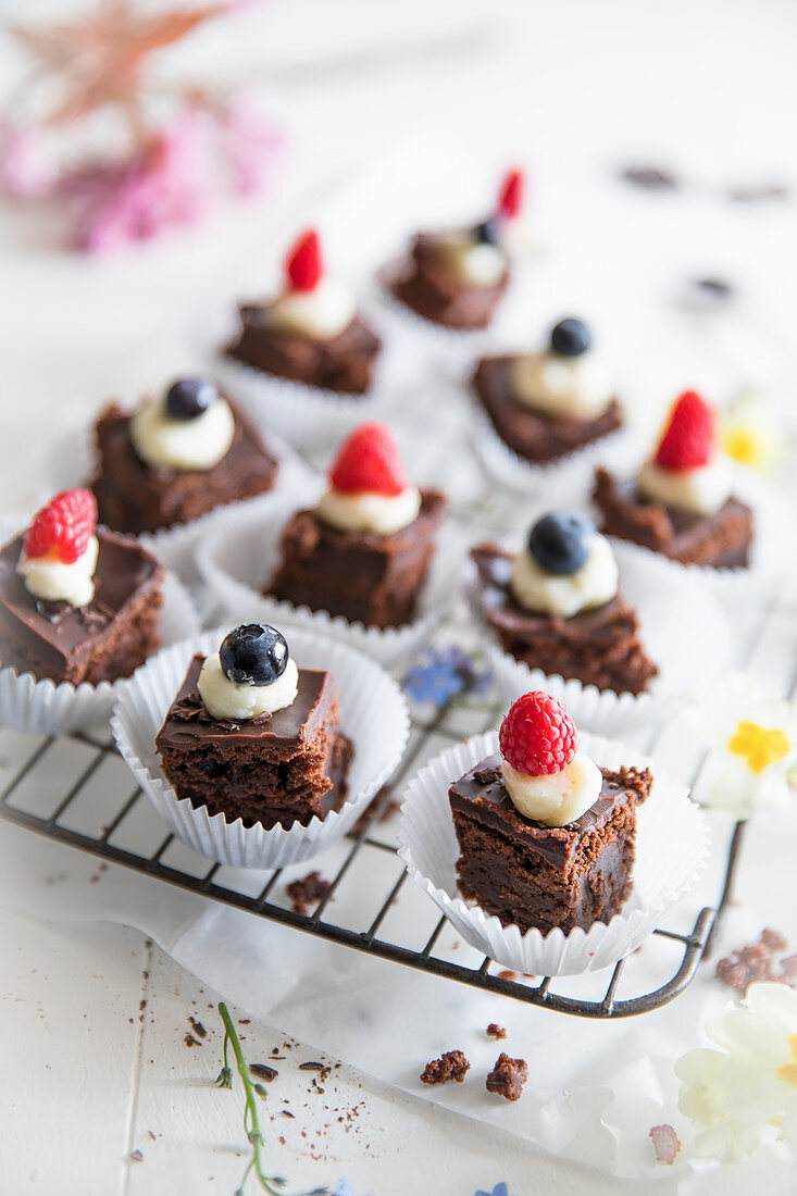 Chocolate brownies topped with white chocolate icing, raspberries and blueberries