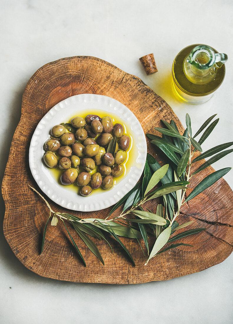 Eingelegte grüne Oliven und Zweige auf Olivenholzbrett