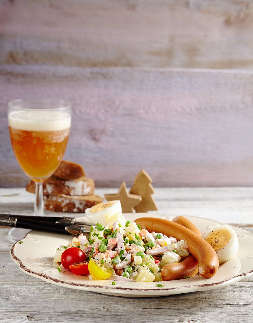 Sausages, potato salad with diced vegetables, peas and mayonnaise and a hard-boiled egg