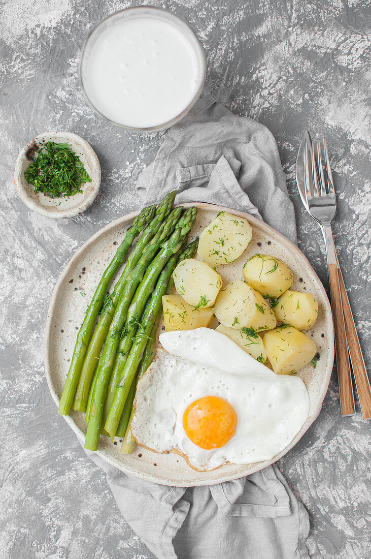 Fried eggs with dill potatoes and cooked green asparagus