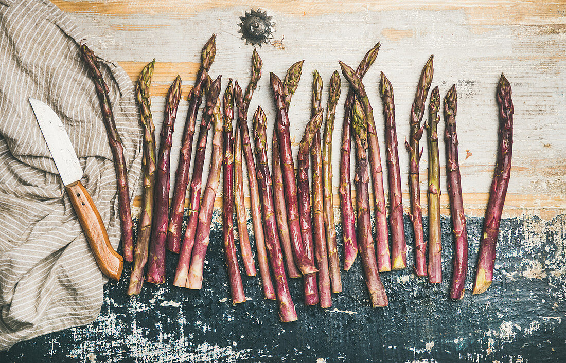 Purple asparagus in row over rustic wooden background