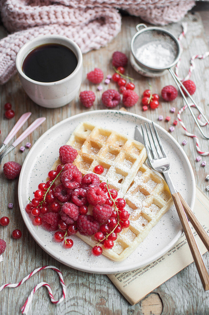 Waffles topped with red currants and raspberries served with cup of black coffee