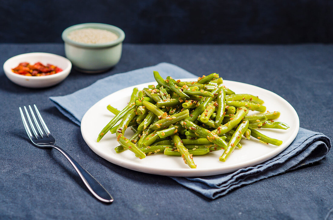 Plate of stir fried green beans with sesame seeds on a blue background