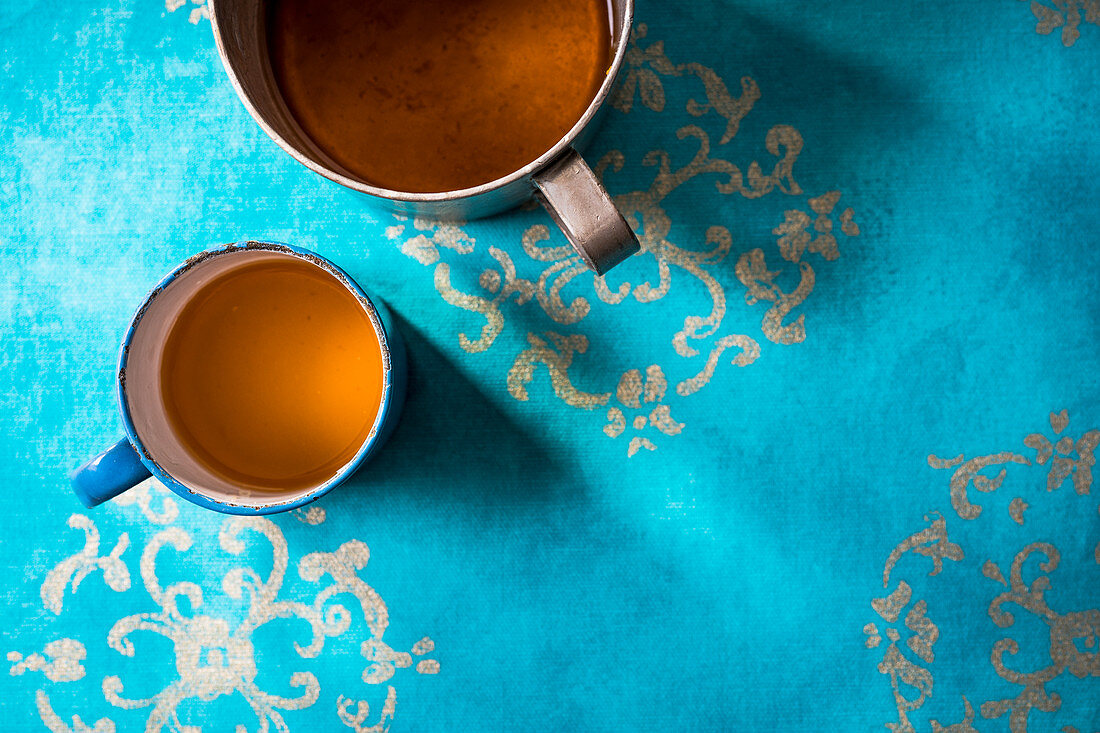 Coriander and ginger tea in a metal cup on an azure blue surface