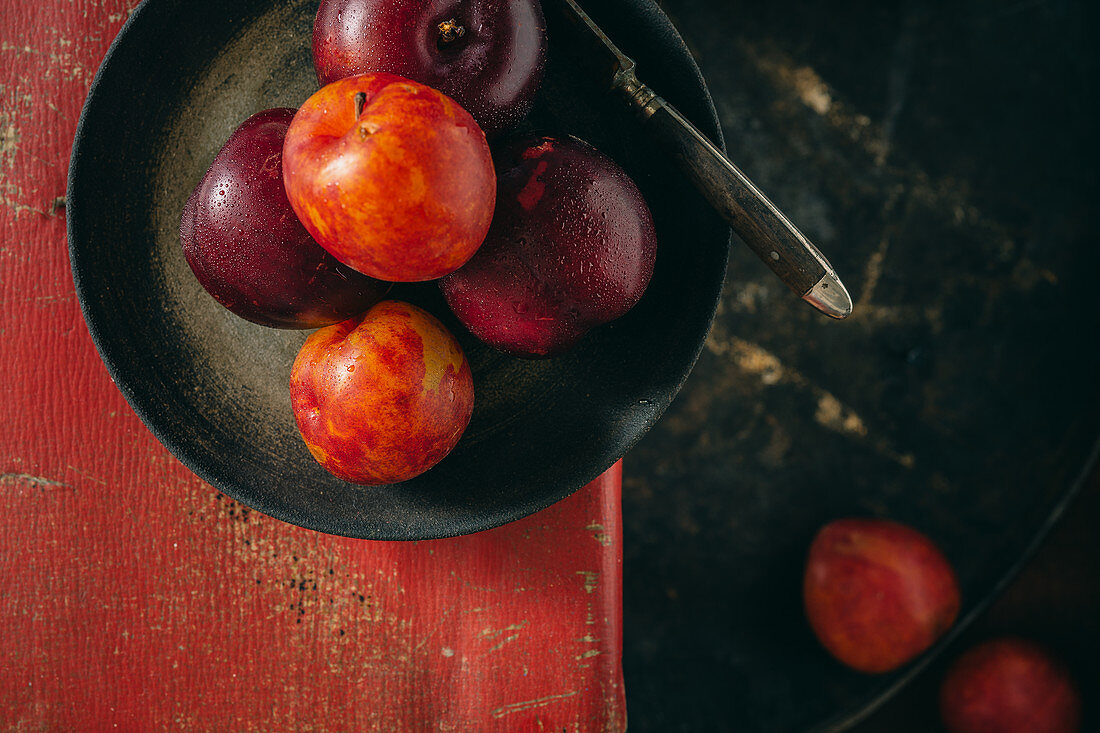 Various different coloured plums in a black pan