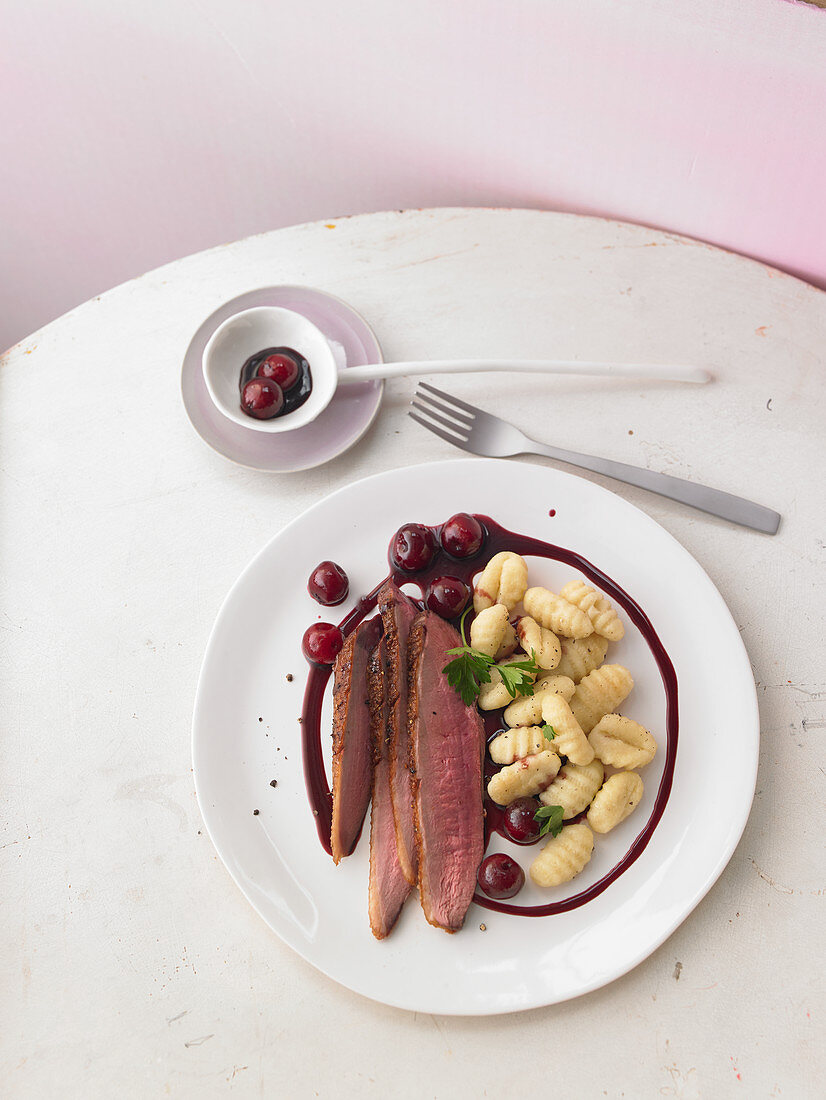 Crispy duck breast in a spicy balsamic reduction with cherries and gnocchi