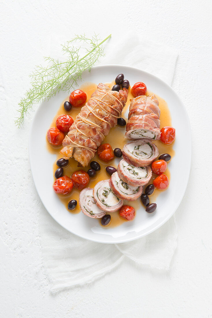 Saddle of rabbit wrapped in bacon with olives and cherry tomatoes