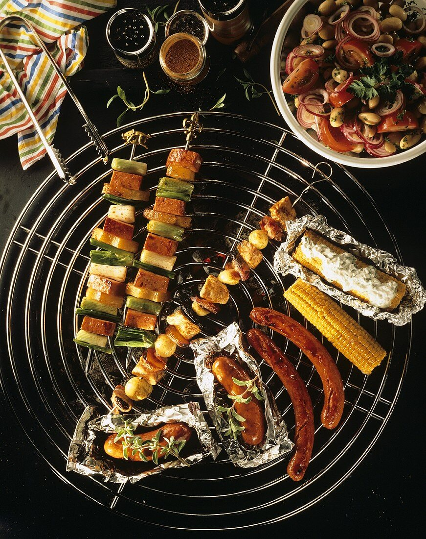 Grilled corn cobs, sausages & kebabs on grill; bean salad