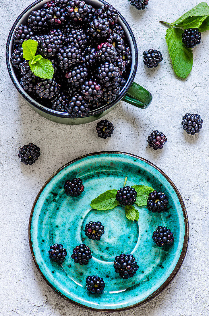 Blackberry harvest in an iron mug and a saucer on a concrete background