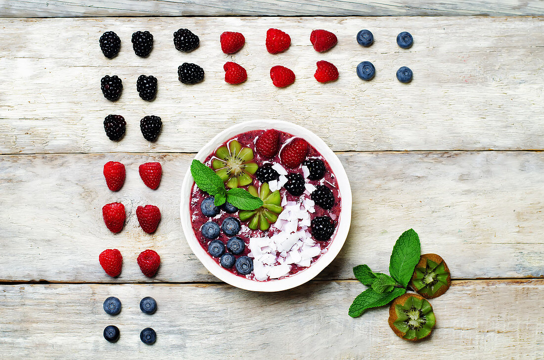 Blueberry smoothies breakfast bowl with coconut flakes, raspberry, blueberry and blackberry