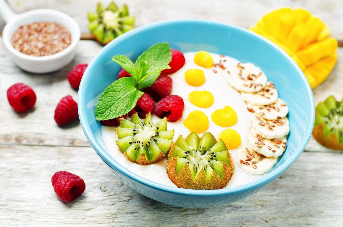 Breakfast oatmeal porridge with kiwi, mango, raspberry, banana and flax seeds
