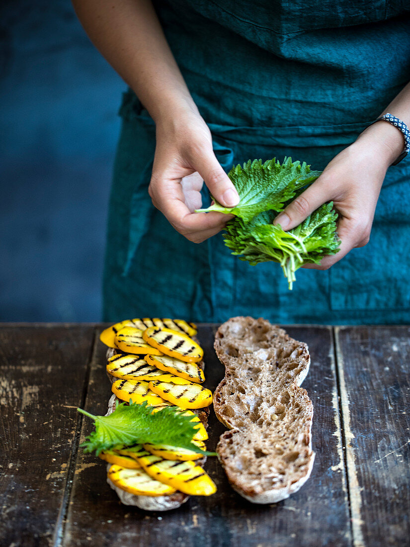 Ciabatta bread being topped with grilled yellow courgette and shiso leaves