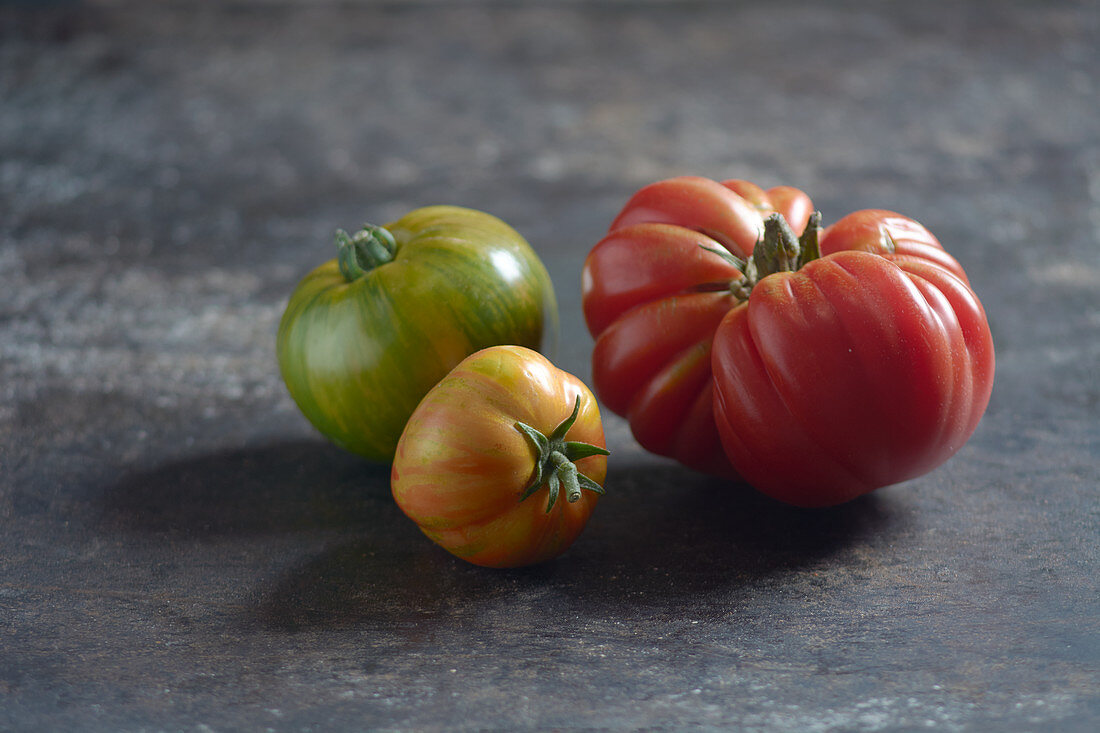 Zebra tomatoes and an ox heart tomato on a sheet metal
