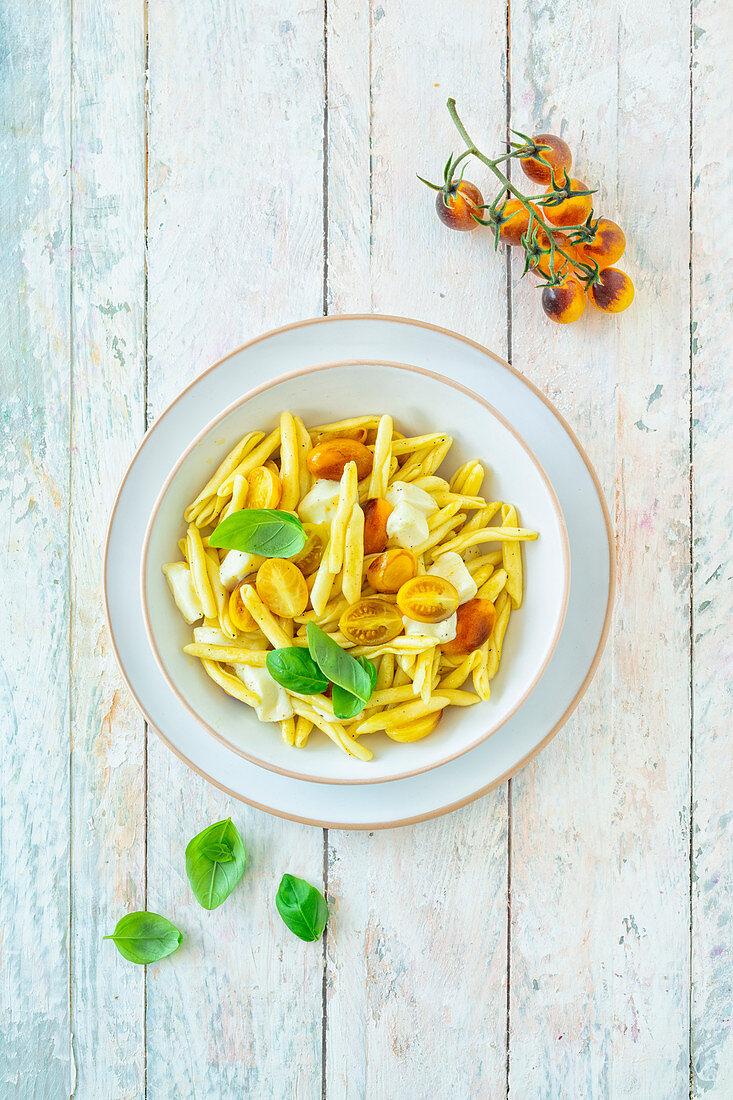 Macaroni with yellow tomatoes, mozzarella and basil